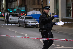 © Licensed to London News Pictures. 10/04/2021. London, UK. A police officer maintains a cordon after a 17-year-old boy was fatally stabbed in Sydenham. Police were called to Hazel Grove, junction with Sydenham Road, at 19:19BST on Saturday, 10 April after reports of a male lying injured on the ground. Officers attended with medics from the London Ambulance Service and the London Air Ambulance. They found a 17-year-old male who had been stabbed. Despite the best efforts of the emergency services, he was pronounced dead shortly after 20:00BST. Photo credit: Peter Manning/LNP