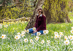 © Licensed to London News Pictures. 01/04/2021. London, UK. Flora Lawrenson, 29, from Southfields enjoys the spring flowers and sunshine in Cannizaro Park, Wimbledon Village, South West London as weather forecasters predict a much cooler outlook for the Easter period from tomorrow with temperatures down by 10c and even the possibility of snow in parts of the country. Photo credit: Alex Lentati/LNP
