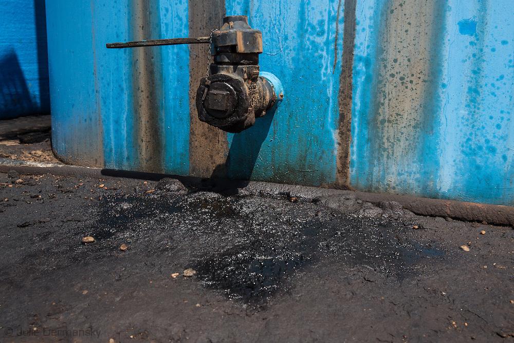 Oil leaking on the ground at oil tanks in Kingsman County Kansas.