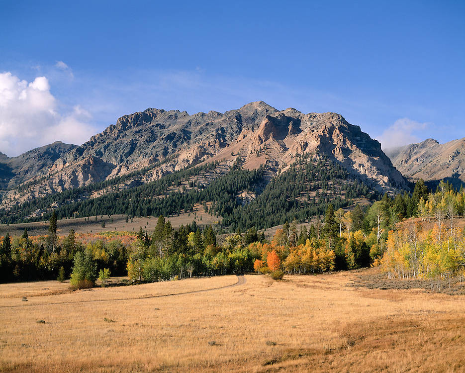 Boulder Mountains and road to Ghost Town of Boulder City in foreground with early fall colors. Licensing and Open Edition Prints.