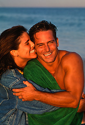 woman  playfully biting a man's ear while at the beach in East Hampton, NY