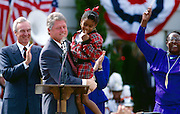 President Bill Clinton lifts an African American child after speaking at a political rally in Macon, Georgia. Behind Clinton is Senator Wyche Fowler (D-GA)