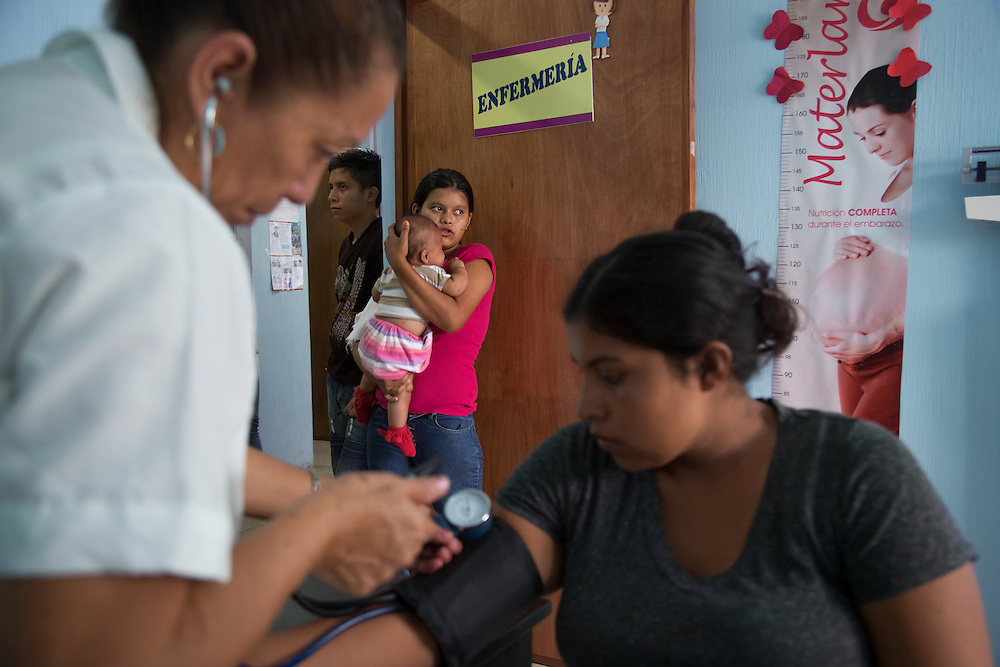 """The vitals of young mothers are taken at the San Benito Youth Clinic. """"To see a girl having to deal with a baby, it is as if she was playing with dolls [but she isn't]. To me that's shocking,"""" said Dr. Sayda Acosta, pediatrician and San Benito Youth Clinic director."""