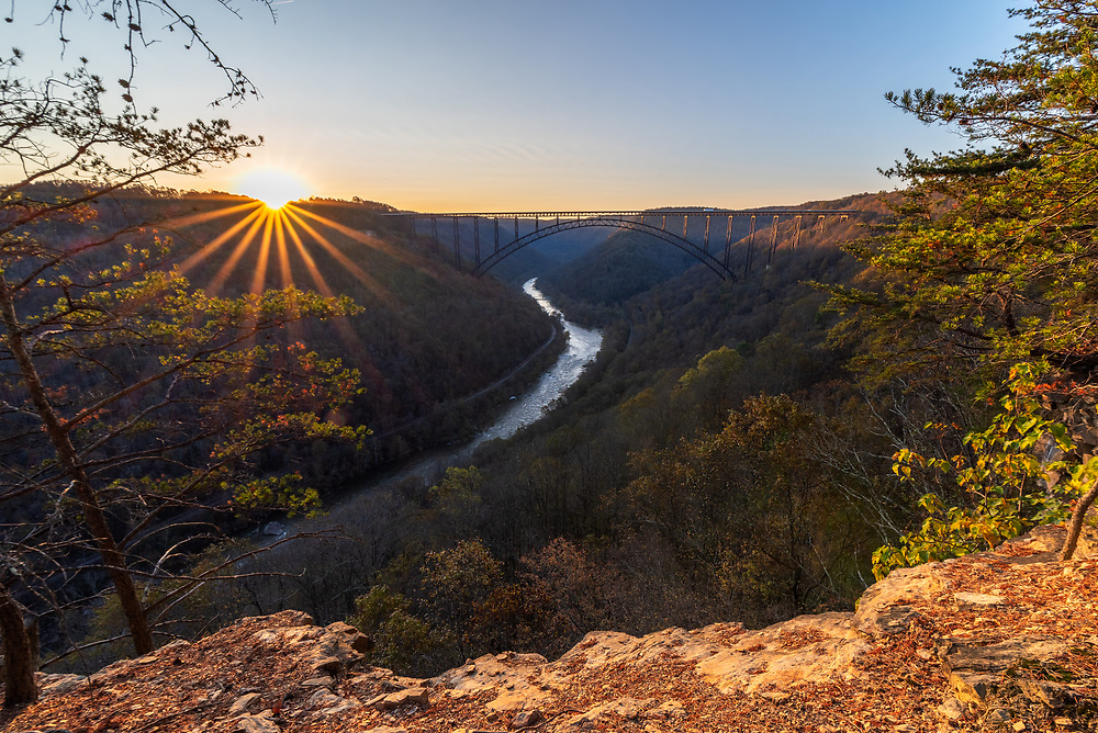 The sun rises above the New River Gorge Bridge on a late autumn West Virginia day from the vantage of a high cliff line.
