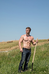shirtless muscular man with a shovel in a field