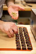 """Xocolatl Chocolate, where owner David Briggs preparing the """"Chevre Ganache"""" which is ganache mixed with River's Edge Chevre cheese.  Each piece is carefully garnished with a Pepitas (pumpkin seed) - the reasoning for the garnish is that the dairy feed it's goats pumpkins as part of their diet."""