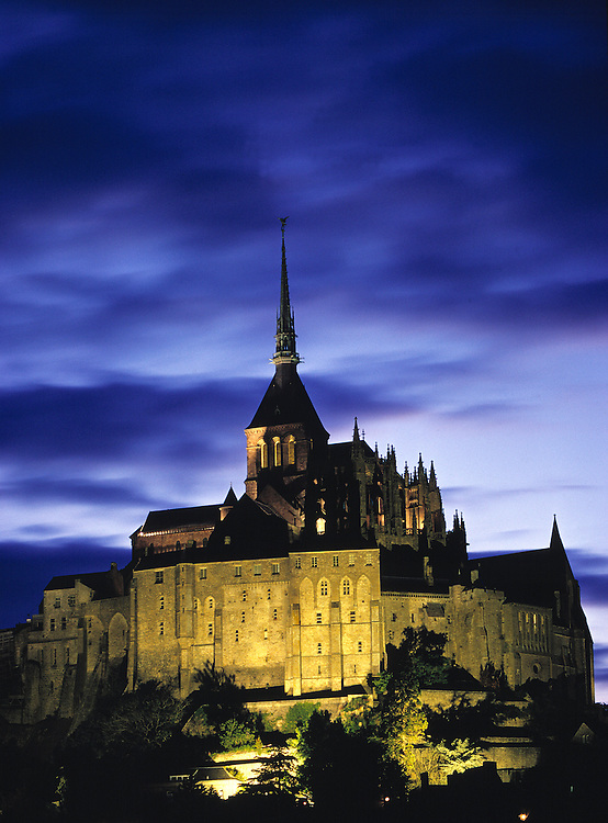 Flood lights add relief to the interesting architecture of Mont St. Michel in Normandy, France.