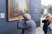 Members of the public admire a copy of Seaport with the Embarkation of Saint Ursula by Claude Lorrain 1641, part of a temporary display of historical art placed outside the National Gallery to show passers-by what can be seen in their galleries, on 1st September 2021, in Trafalgar Square, London, England.