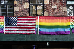 """August 26, 2017 - New York City, New York, United States of America - American and Pride flags together across from the Stonewall Inn. Dozens demonstrated for Kiwi Herring, a 30 year old trangender woman that was shot and killed by St. Louis police after a call from a neighbor. The demonstration eventually became a march that snaked through lower Manhattan, making stops at restaurants to deliver the message to the patrons.  At least one verbal altercation transpired. The family of Herring alleges that she was the victim of long-term harassment by a """"homophobic"""" neighbor, while the police allege that she held a knife and injured at least one officer with it.  Prior to the fatal incident, there was another knife incident on the premises involving Herring and a neighbor.  ..Currently, police are investigating and if non-lethal methods were used before the fatal shooting.  The Human Rights Campaign, a gay rights NGO, has stated that this is the 18th transgender killing this year, with nearly all the victims being people of color, and nearly all having been black.  Furthermore, just one day prior, Trump signed the bill banning transgender people from serving in the military. (Credit Image: © Sachelle Babbar via ZUMA Wire)"""