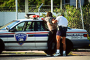A Miami Beach police officer searches a suspect in Miami, Florida