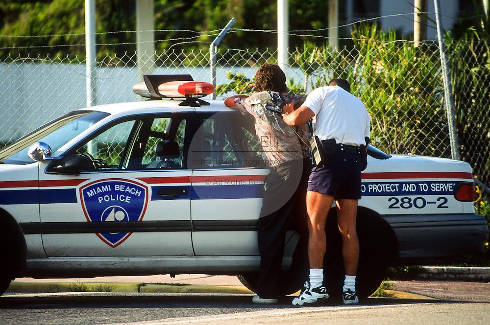 A Miami Beach police officer searches a suspect in Miami, Florida