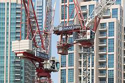 Construction cranes on construction site building new high rise apartment towers in Downtown Dubai, UAE, United Arab Emirates,