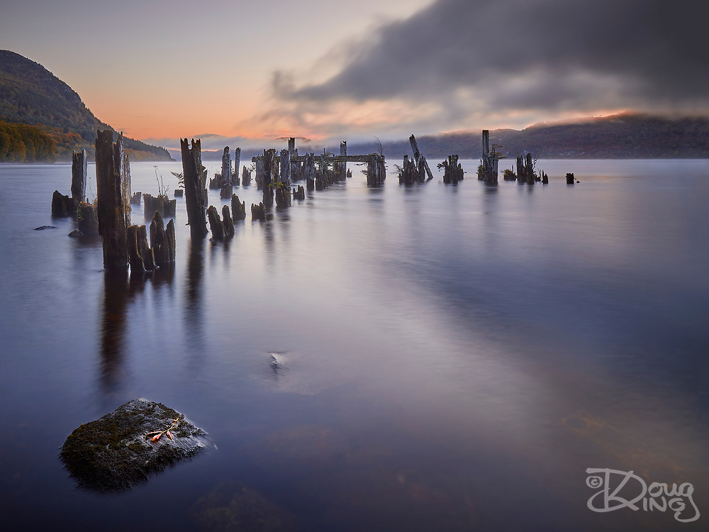 I spotted these rotting remains in Loch Ness momentarily from the road approaching Invermoriston and vowed to return the following morning to photograph them. A little research that evening revealed the remains to be a former steamer pier from the days that steamers plied the Caledonian Canal and Loch Ness from Glasgow to Inverness. The dawn turned out to be near perfect for photography and mother nature added the final touch for me - a fallen autumn leaf on the bounder in the foreground.