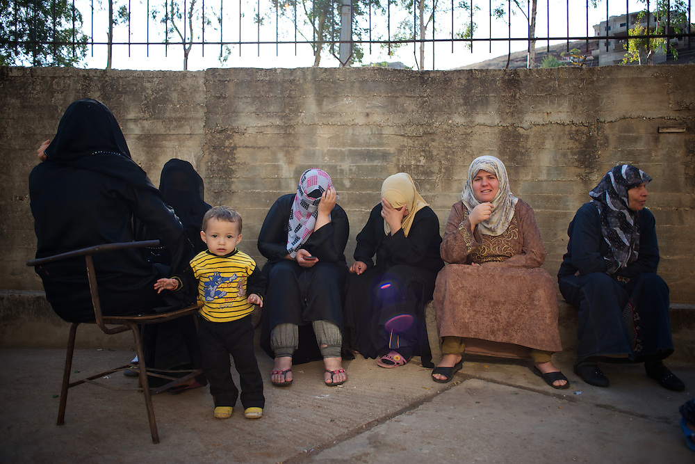 A group o Syrian women and a child sitting in a patio a refugee center in Wadi Khaled, Lebanon.