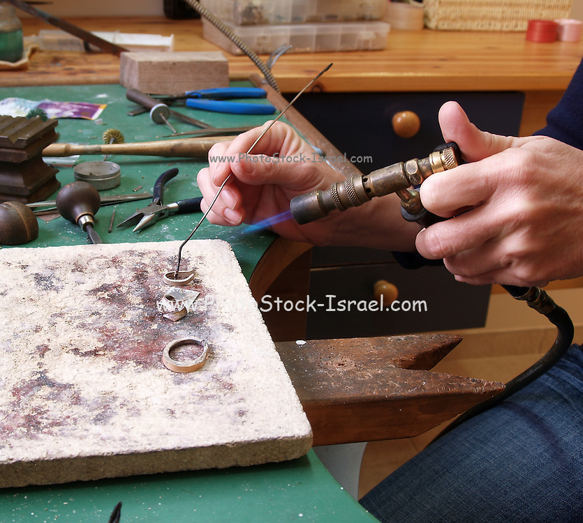 Jeweller forms a ring with a blowtorch