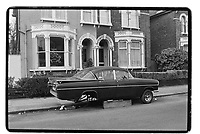 Car with wheels missing, South East London, 1982. South-East London, 1982