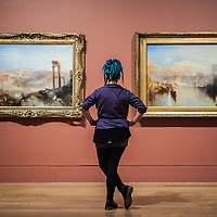 London, UK - 8 September 2014: a gallery assistant poses next to 'Modern Rome - Campo Vaccino' (L) and 'Ancient Rome: Agrippina Landing with the Ashes of Germanicus' (R) by J.M.W. Turner, brought together for the first time in a generation.