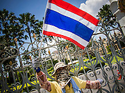 03 SEPTEMBER 2013 - BANGKOK, THAILAND: A person protesting the price of cooking gas blocks the fence in front of Government House in Bangkok. The Thai government raised the price of Liquified Propane Gas (LPG - cooking gas) by 50 satang per kilogram (about 1.5 cents US) over the weekend. The price of electricity and highway tolls also went up on the same day dealing most Thais a triple blow. The Thai consumers foundation has filed a suit in Thai administrative courts to block the increase but the courts have not yet ruled on the case. About 50 people protested the price hike at Government House in Bangkok and delivered a letter outlining their objections to a representative of the Prime Minister.      PHOTO BY JACK KURTZ