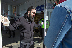 © Licensed to London News Pictures. 22/03/2020. London, UK. An employee checks for ID as a key worker is allowed into a Tesco in Hackney, east London.  The shop opened for one hour between 10-11am just for key workers with other shoppers let in in small groups after that time.  Photo credit: Marcin Nowak/LNP