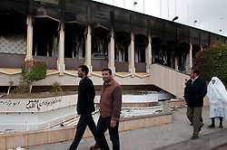 © under license to London News Pictures. 24/02/2011. People walk by Muarmar Gaddafi's burnt out palace at the Army Compound in the Libyan city of Benghazi. Photo credit should read Michael Graae/London News Pictures