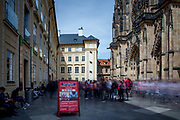 Tourist groups at the inner courtyard of Prague Castle and at the entrance of St. Vitus Cathedral (right). This cathedral is a prominent example of Gothic architecture and is the largest and most important church in the country.