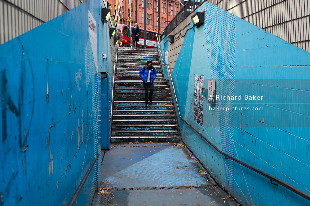 A man wearing a blue puffa jacket descends the underpass steps leading into the Old Street station in Shoreditch, on 4th November 2019, in London, England.