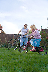Mother and daughter riding bikes in the garden,