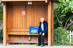 A male pensioner waiting for a bus.