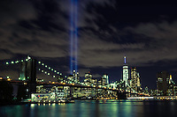 The September 11th Memorial lights shine brightly above New York City, downtown Manhattan and the Brooklyn Bridge.