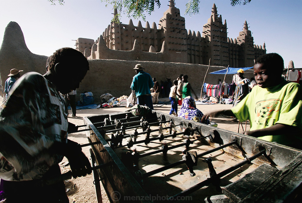 Fuzbol (also spelled fusbol) players and merchants outside the Grand Mosque, Djenne, Mali. Africa, Games, Muslim, Islam, Religion, Africa.