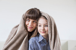 Mother and daughter covered with blanket, smiling