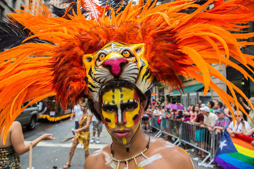 A marcher wears a bright orange headdress in the parade on 5th Avenue.