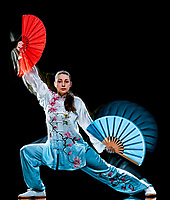 one chinese woman partacticing  Tai Chi Chuan Tadjiquan posture studio shot isolated on black background  with light painting effect