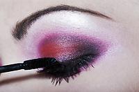 woman applying mascara colored eyeshadow makeup