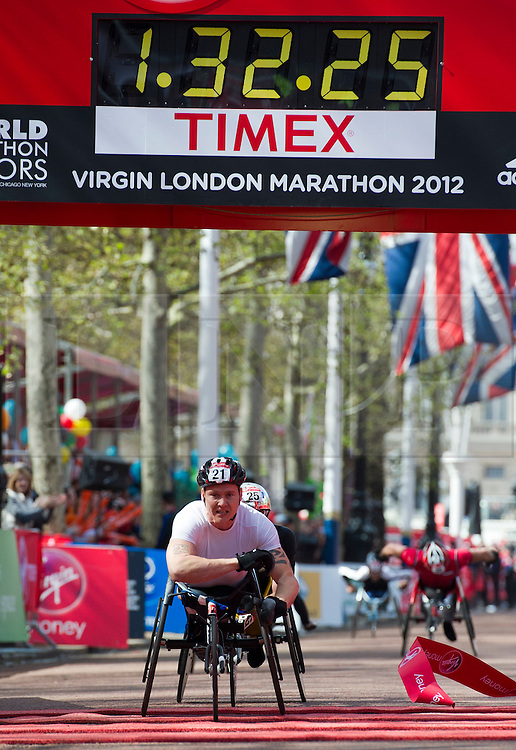 © London News Pictures. 22/04/2012. London, UK. Britain's David Weir crosses the finish line to win his fifth London Marathon wheelchair race at the 2012 Virgin London Marathon on April 22, 2012. Photo credit : Ben Cawthra /LNP