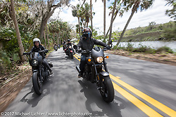 Iron Lilly Kristen Lassen (L) riding a Harley-Davidson Sportster alongside custom bike builder Jesse Rooke through Tomoka State Park during Daytona Beach Bike Week. FL. USA. Tuesday, March 14, 2017. Photography ©2017 Michael Lichter.