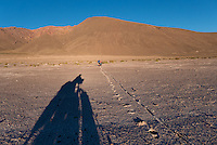 Cyclists pushing their bikes in the volcanic ash close to the Volcano Ollage in Chile, Atacama desert, close to the Bolivian border