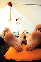 A man relaxes in his tent after a long hike in the Tatoosh Range of Mount Rainier National Park, Washington.