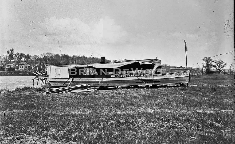 """Location unknown. """"Dewey"""" is name of boat. Only two words on the sign atop the boat are discernible: """"Boat"""" and """"Batavia"""".<br /> <br /> This picture might have been taken at Laurelwood Park or Mill Creek Park. These parks, described in John Gustafson's """"Historic Batavia"""" were """"going"""" places in the late 1800's. There are similar boats in pictures taken around the time this shot was taken."""