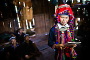 """Hap at her family home, wearing the dratitional dress of the Dao ethnic minority and a hat in family possession that is used as part of the traditional wedding dress. Hap reading in her English school book. Portrait of Hap, 14, who is part of the Plan (NGO) Project """"Because I am a Girl"""" Ban Luoc commune, Hoang Su Phi District, Ha Giang Province, Vietnam, September 2014"""