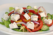 Greek Salad with Feta Cheese containing tomatoes, cucumbers, lettuce, peppers and black olives Seasoned with Zaatar