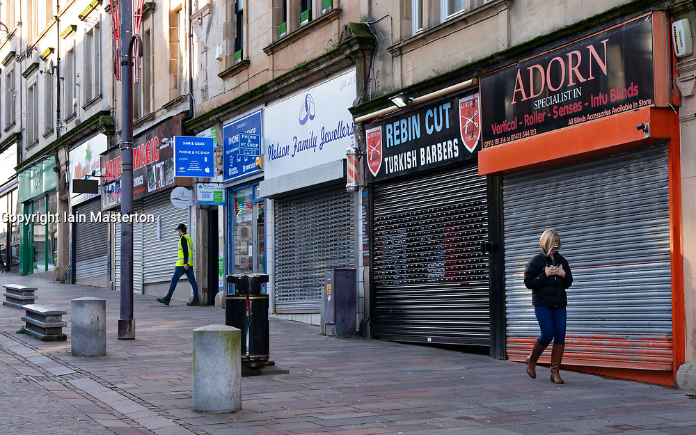 Hamilton, Scotland, UK. 25 November 2020. Hamilton in South Lanarkshire, very quiet during severe level 4 lockdown imposed by the Scottish Government.  Non essential businesses , bars, restaurants and shops are closed. Much of the central regions of Scotland are under the highest level of lockdown.  Pictured; row of closed and shuttered shops in town centre. Credit.  Iain Masterton