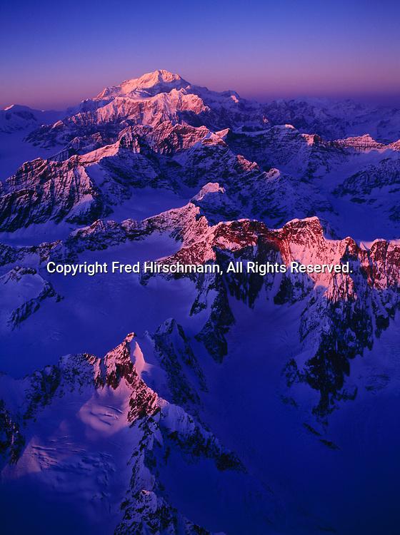 Aerial view of winter sunset illuminating peaks of the Alaska Range east of the Kahiltna Glacier leading toward Mount Hunter and Mount McKinley, Denali National Park, Alaska.