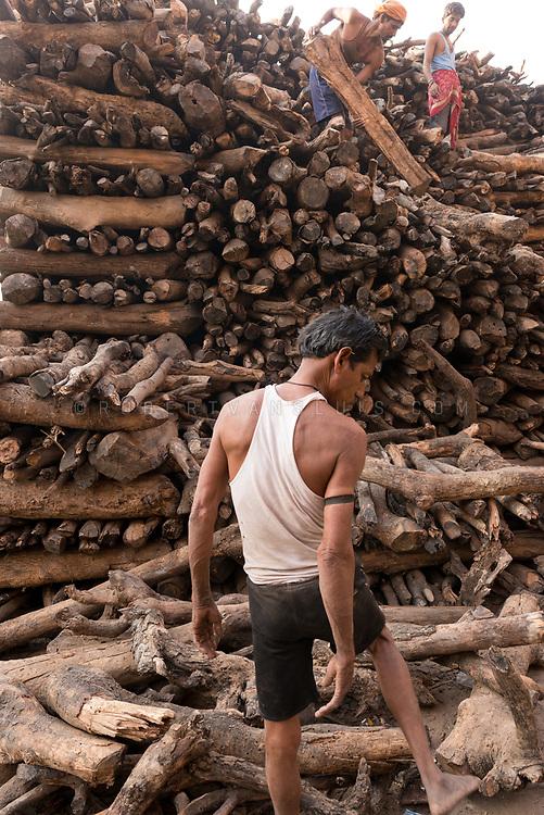 Three men sort out a pile of firewood near Manikarnika cremation ground, Varanasi, India. Photo ©robertvansluis.com