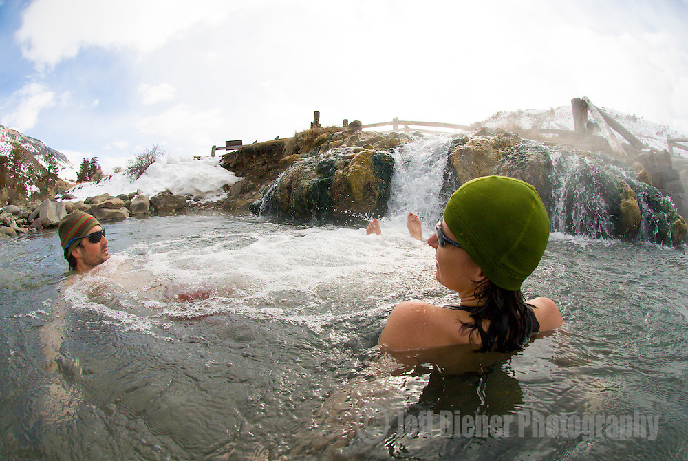 A young couple relaxes in the thermal waters of the Boiling River in Yellowstone National Park, Wyoming.