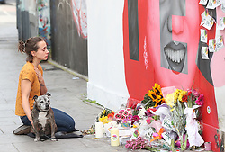 A woman sits in front of a mural of Savita Halappanavar in Dublin as votes are counted in the referendum on the 8th Amendment of the Irish Constitution which prohibits abortions unless a mother's life is in danger.