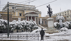 """A person walks in the snow, in the center of Athens, during a rare heavy snowfall in the city on February 16, 2021. - Greece's weather agency said the """"low temperatures, ice and snowfall"""" would continue on February 16, with the civil protection agency recommending that people avoid travel."""