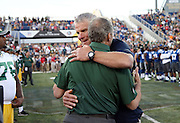 Former Green Bay Packers quarterback Brett Favre hugs a Packers coach as he walks onto the field as a new member of the Pro Football Hall of Fame before the 2016 NFL Pro Football Hall of Fame preseason football game against the Indianapolis Colts on Sunday, Aug. 7, 2016 in Canton, Ohio. The game was canceled for player safety reasons due to the condition of the paint on the turf field. (©Paul Anthony Spinelli)