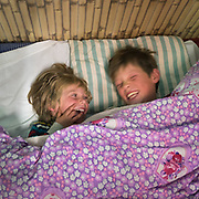 Two young brothers laughs while laying in bed.