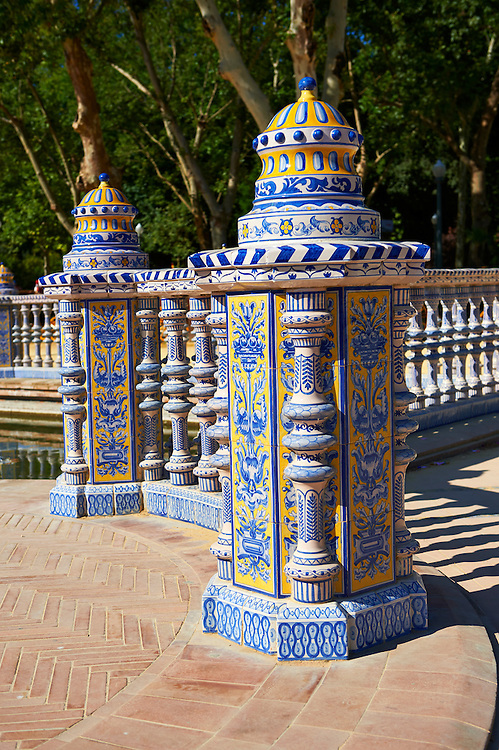 Tiled architectural details of the Plaza de Espana in Seville built in 1928 for the Ibero-American Exposition of 1929, Seville Spain . The Royal Alcázars of Seville (al-Qasr al-Muriq ) or Alcázar of Seville, is a royal palace in Seville, Spain. It was built by Castilian Christians on the site of an Abbadid Muslim alcazar, or residential fortress.The fortress was destroyed after the Christian conquest of Seville The palace is a preeminent example of Mudéjar architecture in the Iberian Peninsula but features Gothic, Renaissance and Romanesque design elements from previous stages of construction. The upper storeys of the Alcázar are still occupied by the royal family when they are in Seville. <br /> <br /> Visit our SPAIN HISTORIC PLACES PHOTO COLLECTIONS for more photos to download or buy as wall art prints https://funkystock.photoshelter.com/gallery-collection/Pictures-Images-of-Spain-Spanish-Historical-Archaeology-Sites-Museum-Antiquities/C0000EUVhLC3Nbgw <br /> .<br /> Visit our MEDIEVAL PHOTO COLLECTIONS for more   photos  to download or buy as prints https://funkystock.photoshelter.com/gallery-collection/Medieval-Middle-Ages-Historic-Places-Arcaeological-Sites-Pictures-Images-of/C0000B5ZA54_WD0s